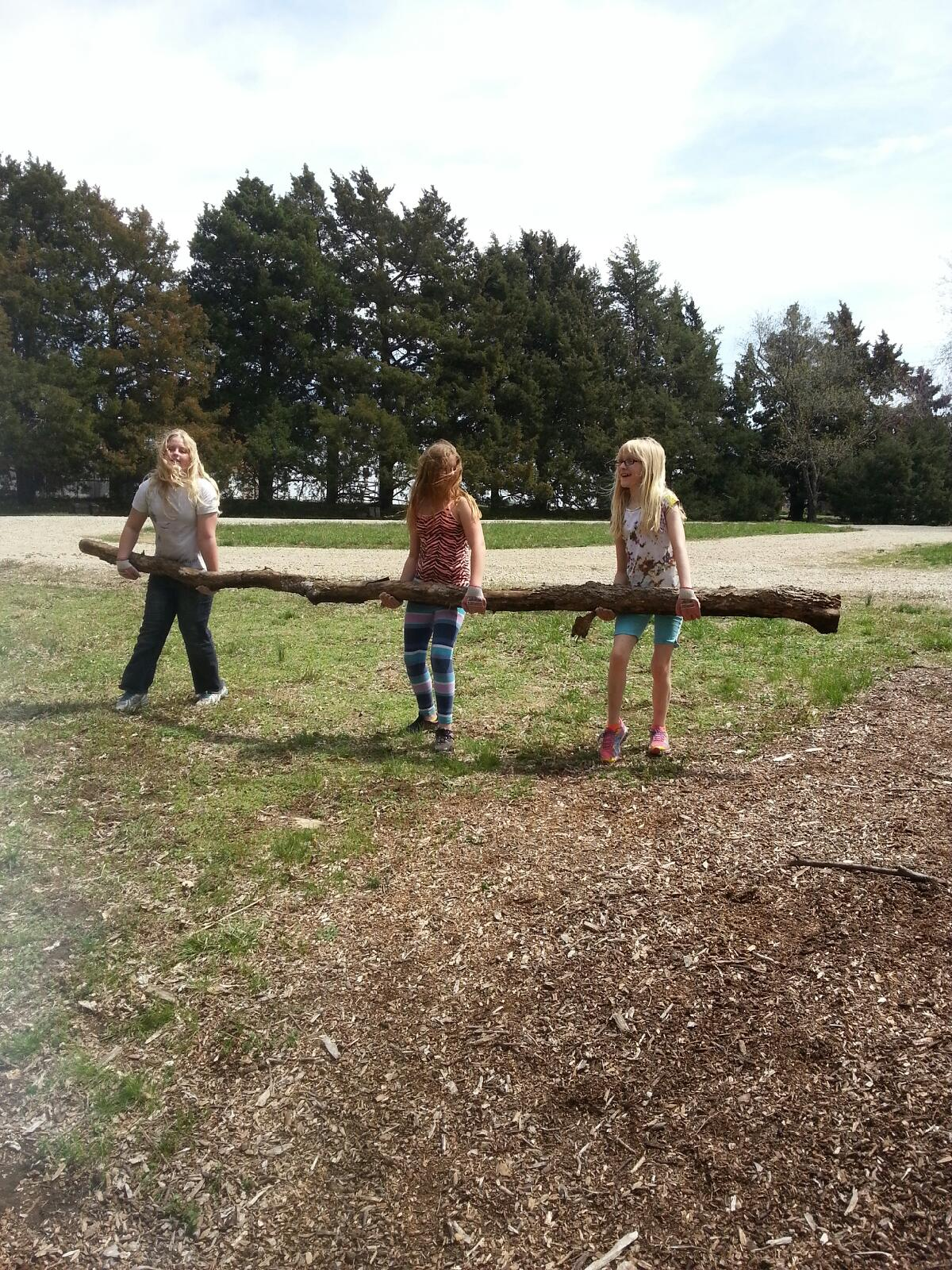 A photo of three girls carrying a large tree limb.