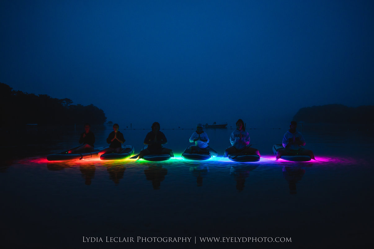yogi's sitting on paddleboards at twilight with underwater lights in a rainbow of color.