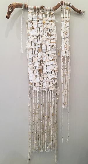 Tissage mural en corde de coton blanc avec inclusions dorées et argentées.