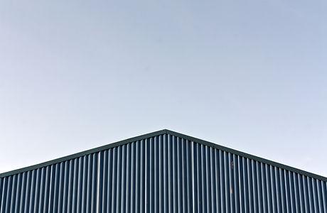 Blue Modern Warehouse Roof Against Blue Sky..jpg