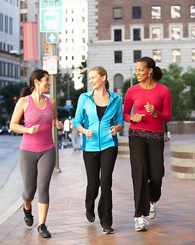 Group Of Women Power Walking On Urban St