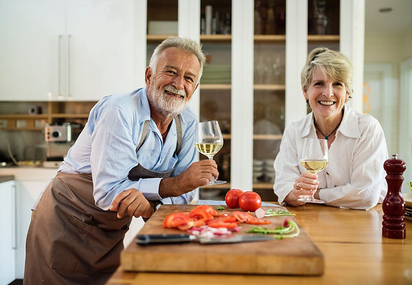 senior couple enjoying wine and chopped tomatoes in a kitchen