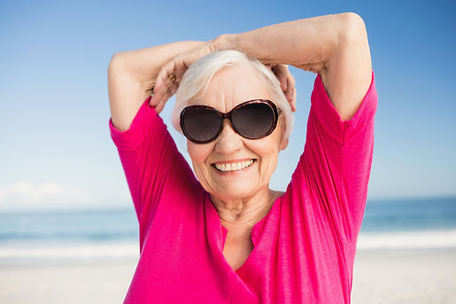 Senior woman with sunglasses looking into camera with ocean behind her