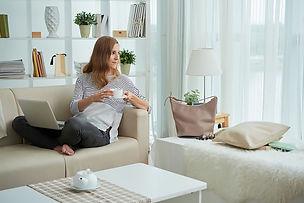 אישה יושבת על ספה בביתה עם לפטופ