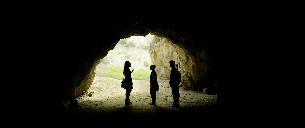 Savitri, Kaeia, and JinJie silhouetted in a cave