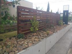 木製フェンスと自然石