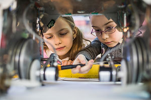 Two-little-engineers-working-in-team-whi