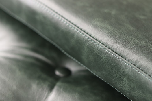 Close up of green leather seat cushions showing top stitching