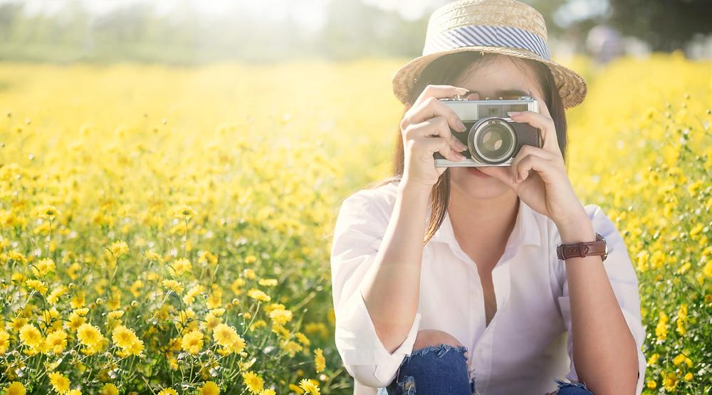 Moça fotografando em um campo florido.