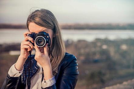 Moça fotografando com uma máquina compacta
