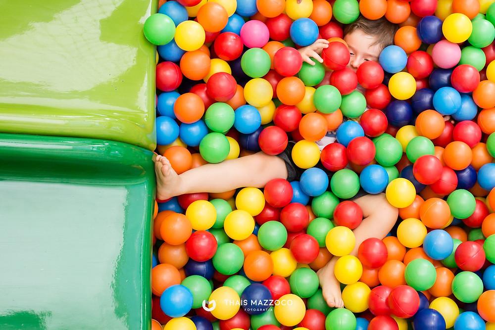 Criança mergulhada numa piscina de bolinhas