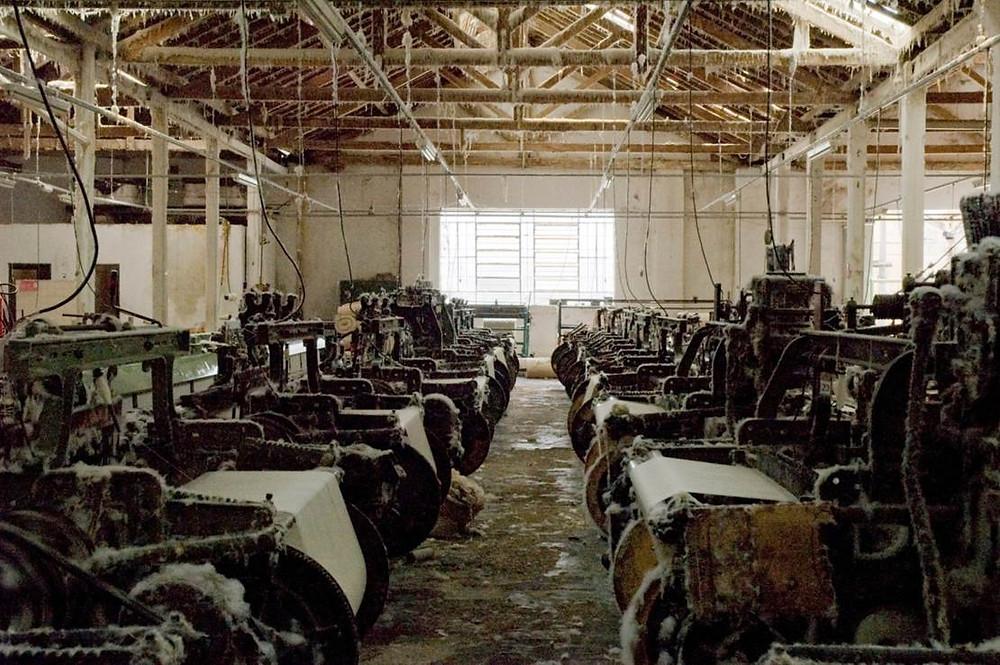 sequencia de teares dentro de barracão de tecelagem