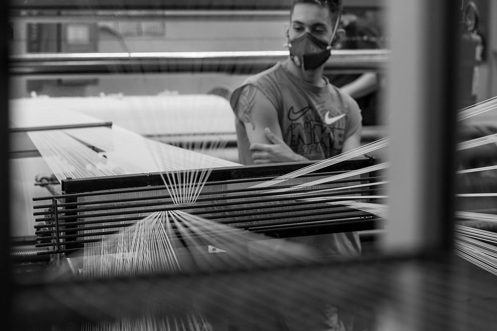 operário de tecelagem é visto trabalhando entre as linhas do tear