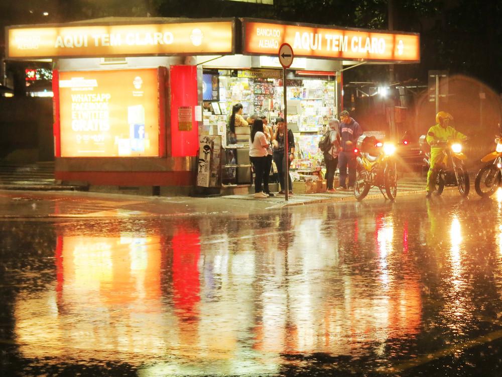 Fotografia noturna em uma noite de chuva de uma cidade. Aparece na imagem uma banca de jornal, algumas pessoas e um funcionário da setransp.