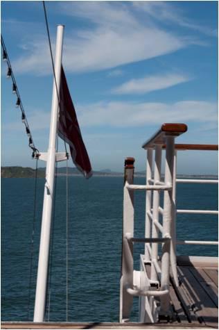 Vista marinha com bandeira e balaustrada do navio.