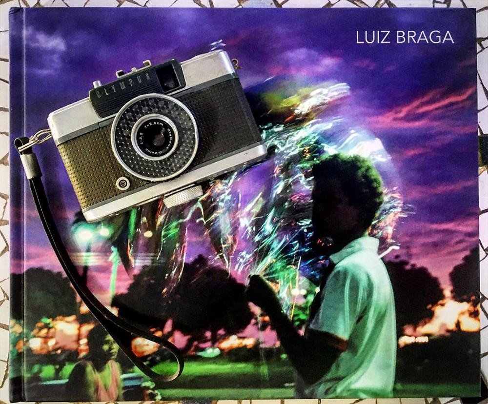 Um livro de fotografia de Luiz Braga com uma máquina fotográfica em cima. Na capa do livro existe uma fotografia de um menino segurando alguns balões em um por do sol