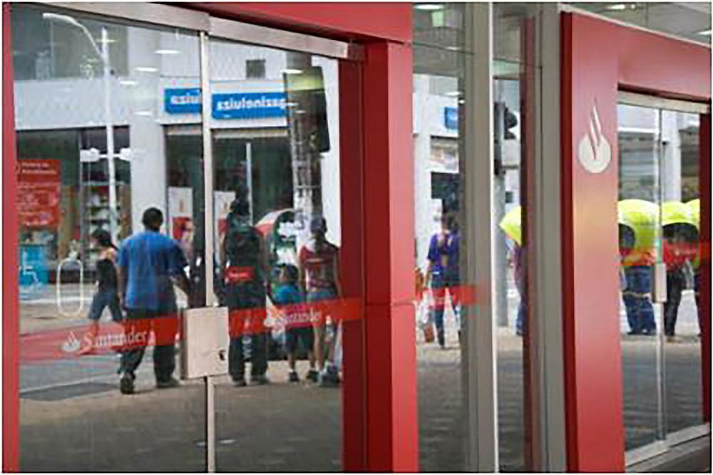 Reflexo na porta de vidro do Banco Santander