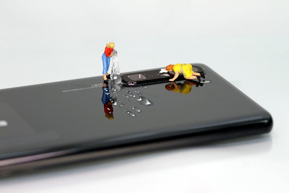miniaturas de mulheres fazem faxina na lente da câmera de um celular