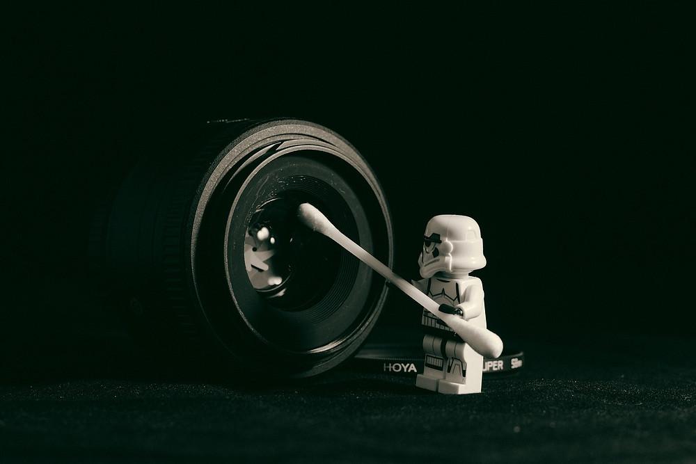 playmobil limpa lente de câmera fotográfica com cotonete