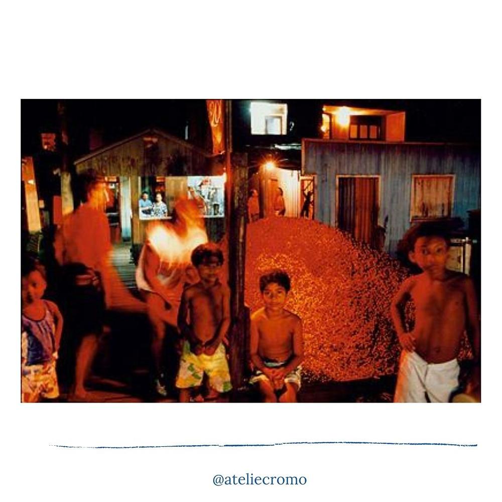 4 crianças em uma venda de açaí. Atrás destas aparece um monte de açaí e ao lado a aparecem dois homens com a imagem um pouco borrada pelo movimento deles. A cena é noturna, a imagem tem um tom alaranjado. No fundo da imagem vemos do lado direito uma casa azul de madeira e do lado esquerdo um barzinho também em uma casa de madeira com um casal dentro.