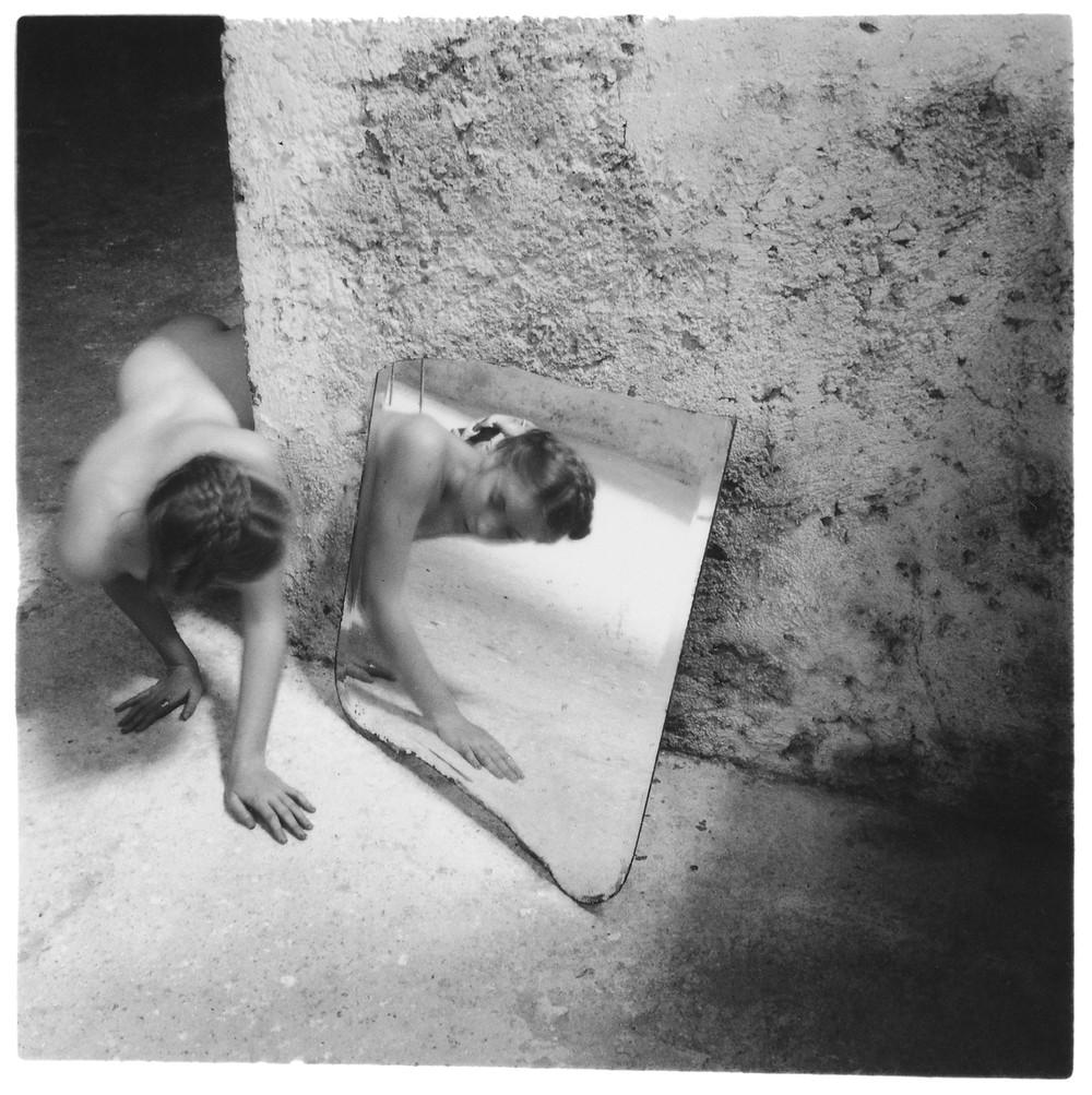 mulher nua engatinha pelo chão e se olha no espelho