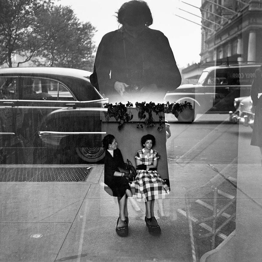 Fotografia de Vivian Maier. Mulher se fotografa no reflexo de uma vitrine.