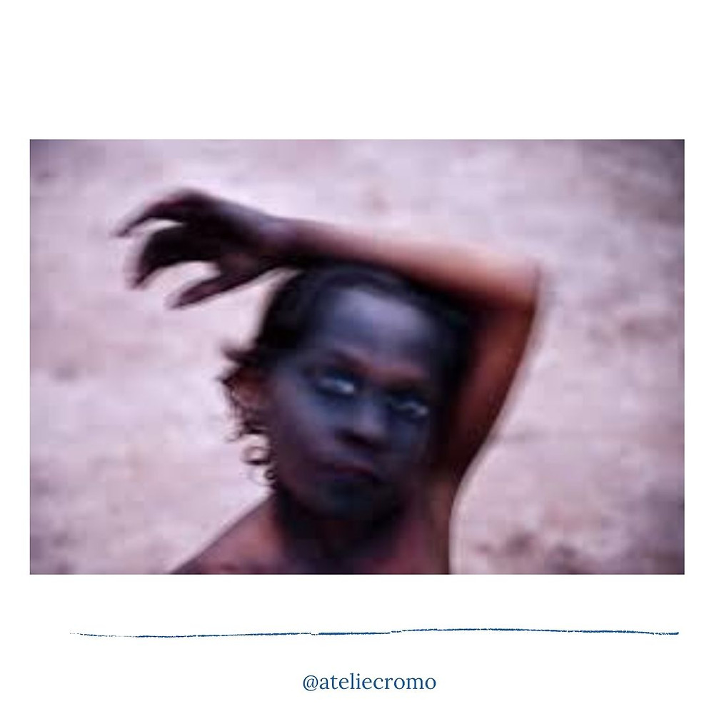 Fotografia de Luiz Braga do rosto de uma menina suja de carvão e com um dos braços apoiado sobre a cabeça. A imagem está meio tremida e chama bastante atenção dos olhos brancos.