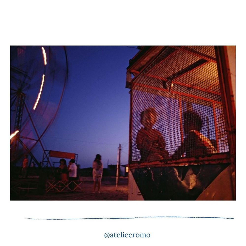 Fotografia de Luiz Braga feita em um parque de diversões em um final de tarde com o céu azul arroxeado. Do lado direito aparecem duas crianças atrás de uma grade e do lado esquerdo uma roda gigante em movimento