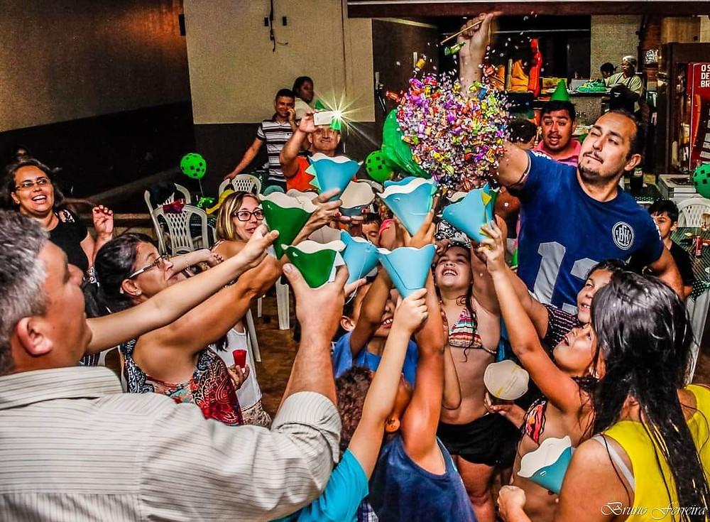 Pessoal comemorando um aniversário, colhem balas de  espalhadas por um balão estourado.