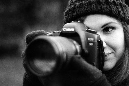 Moça fotografando com uma máquina DSLR