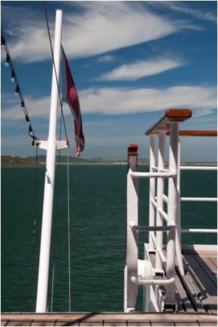 Vista marinha com bandeira e balaustrada do navio., com céu polarizado
