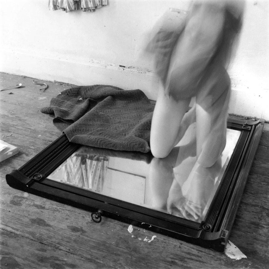 mulher semi nua se movimenta agachada sobre espelho