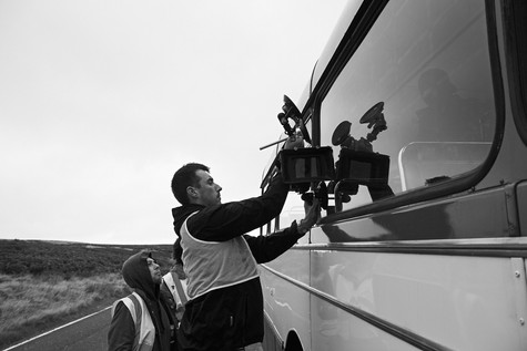 Bobby rigging a camera onto the bus, fingers crossed...