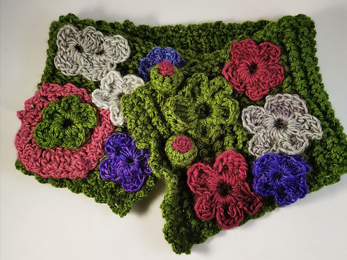 Green crocheted neckwarmer with crocheted bright flowers