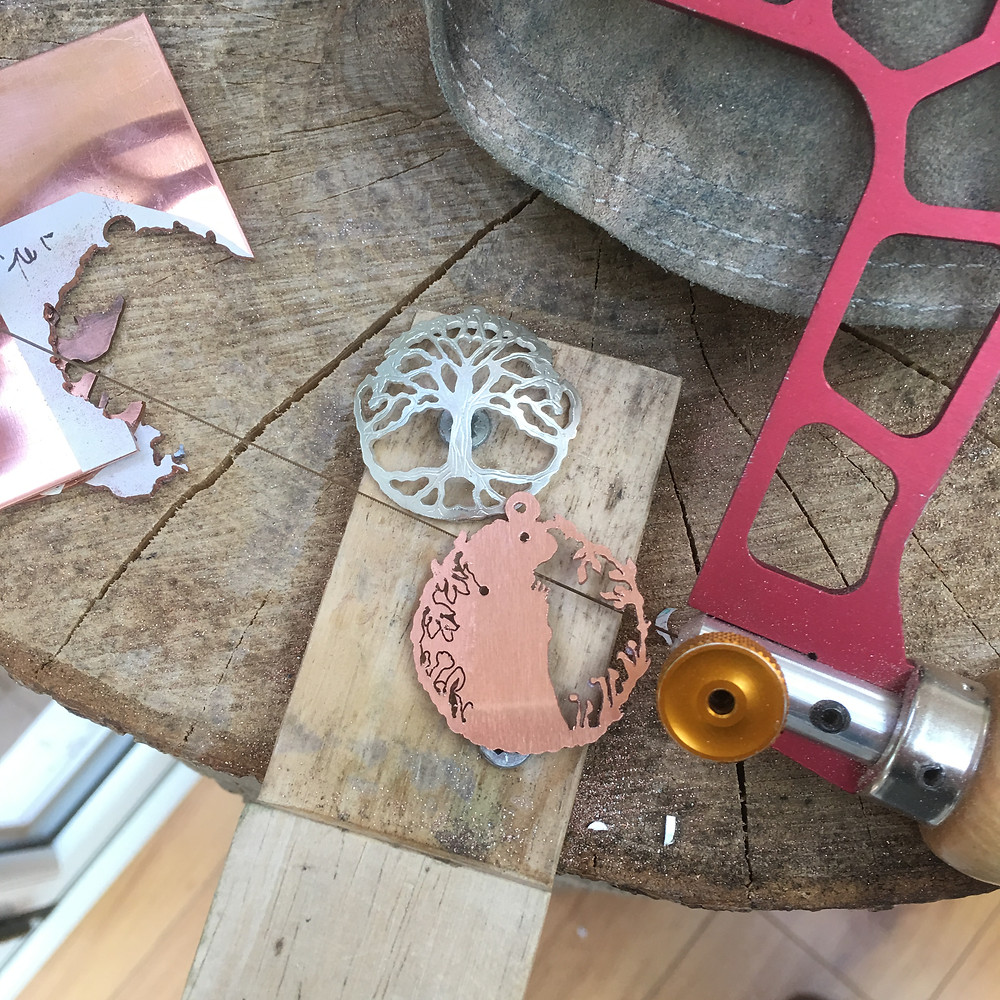 Hand sawn jewellery, made by a human