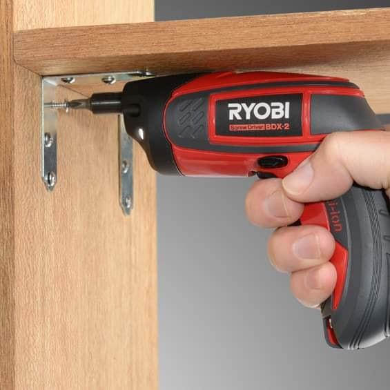 Red screw driver drilling a bookshelf