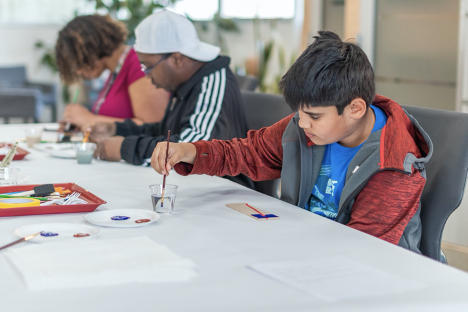 After mapping the trajectory of their families' journey in tape or string, participants re-create that line on a piece of wood--adding color or images around their lines.