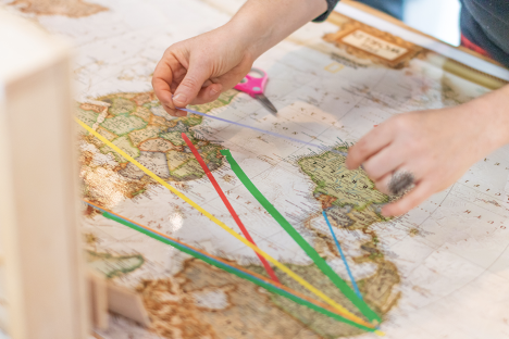 The project begins with a conversation and an invitation. The first step is an invitation to map their family history onto either a map or globe using tape or string.