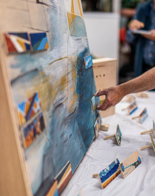 Dreaming in Two Lands  with interactive community elements. A rod was added to the back of each painting, and holes were drilled inside the larger painting. In this way, the work can only be complete with the stories of the community in place.