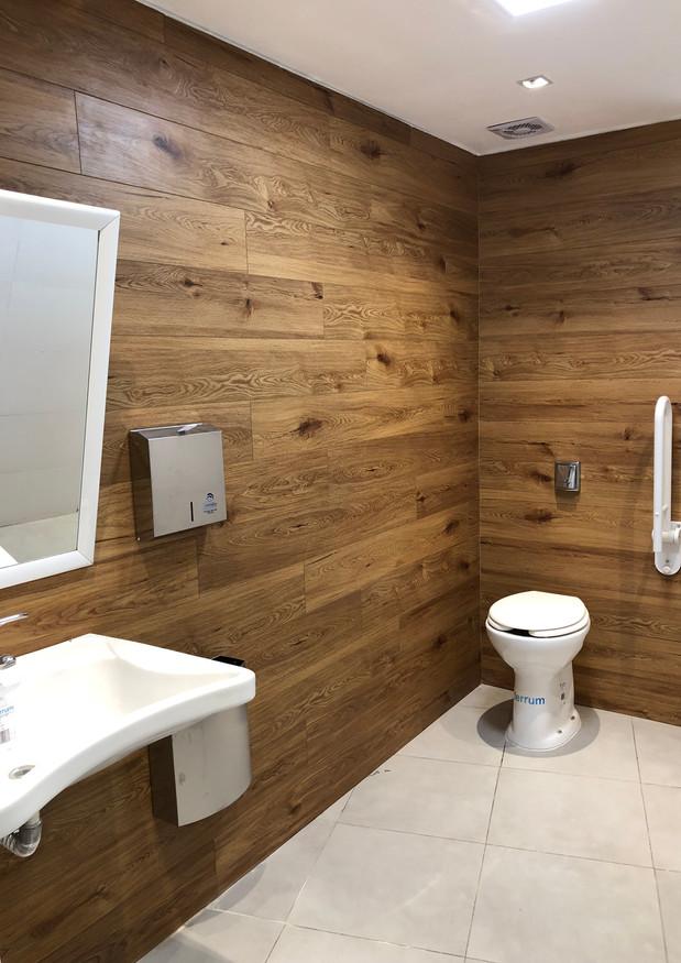 Interior Baño de discapacitados con luminarias led bidireccional y revestimiento vinílico Nogal en muros
