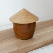 A different type of design, the Utile base has a cone tipped oak lid.