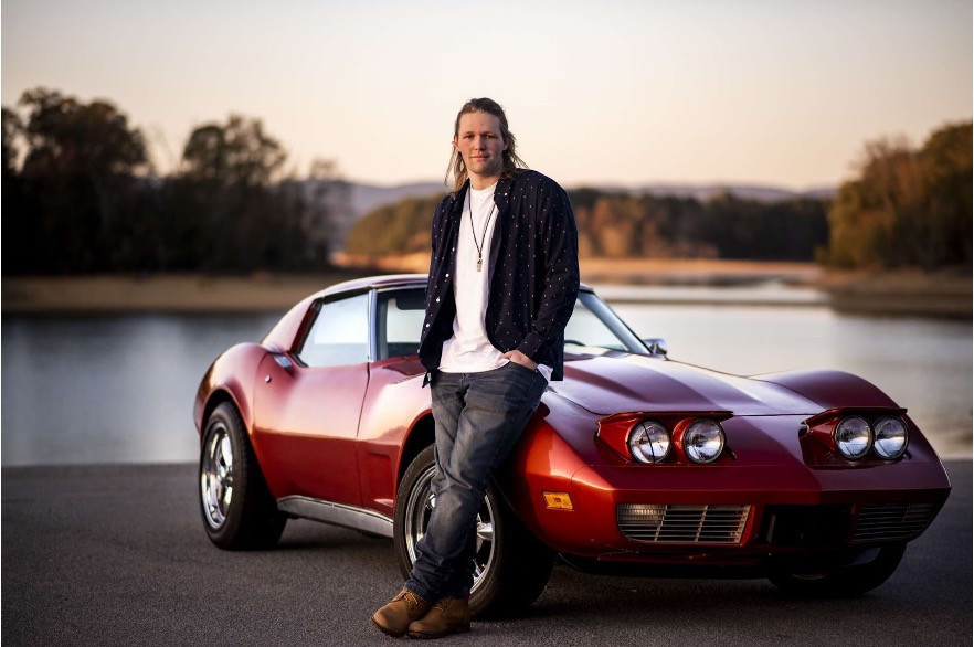AJ Huffman stands proudly next to his 1973 Corvette.