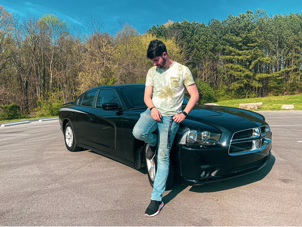 Brandon Goskie stands in front of his 2012 Dodge Charger.