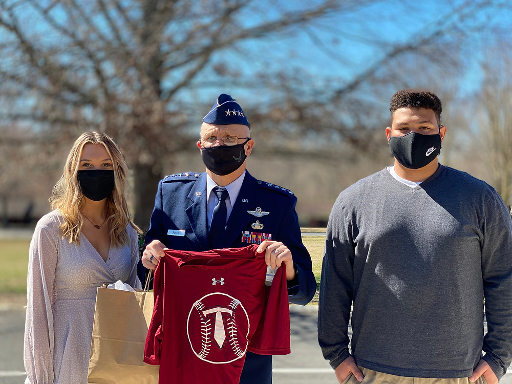 Air Force General Arnold Bunch Jr. holds a baseball t-shirt presented to him by Emmalee Stubblefield and Jaiden Picardi