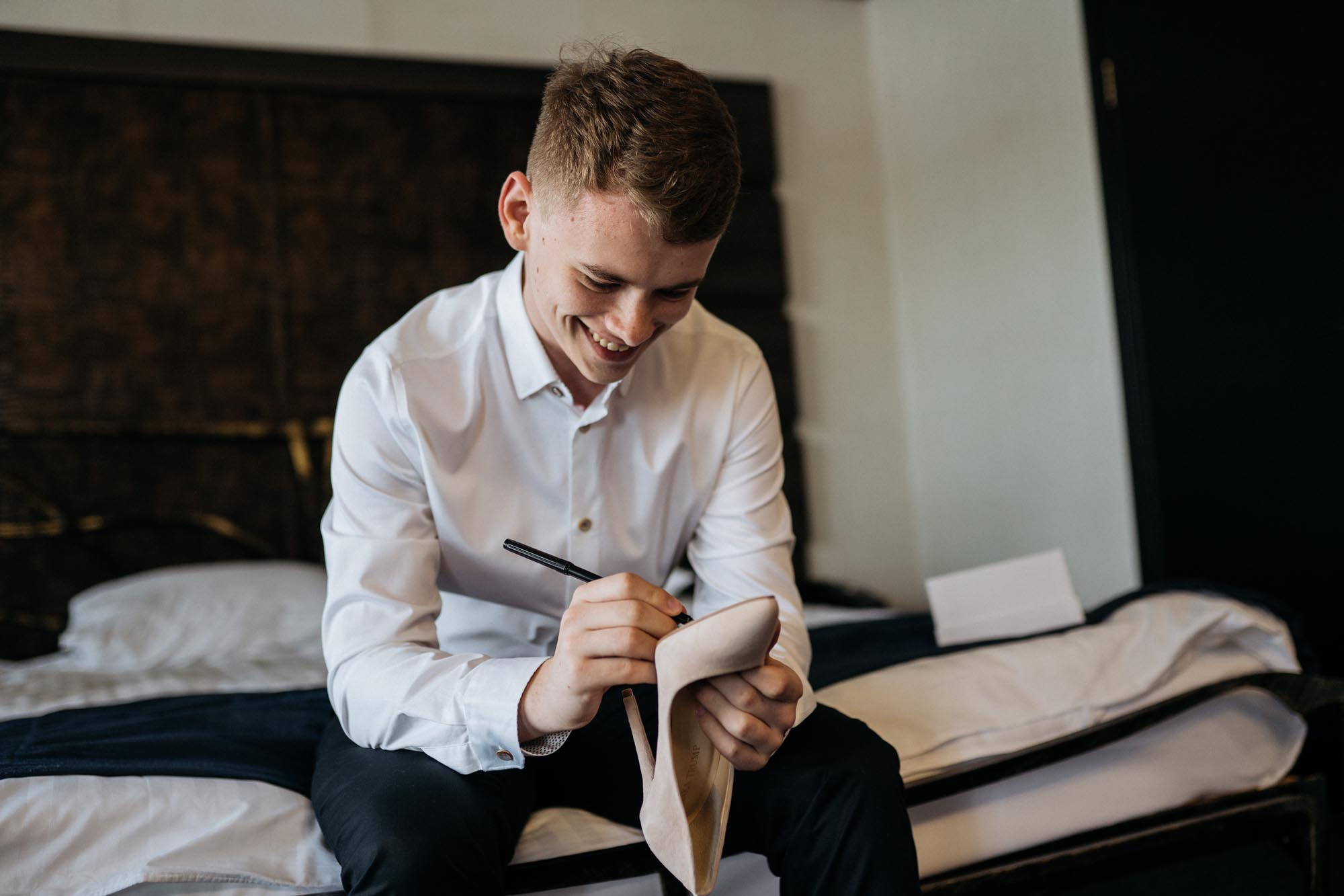 жених пишет на туфли невесты