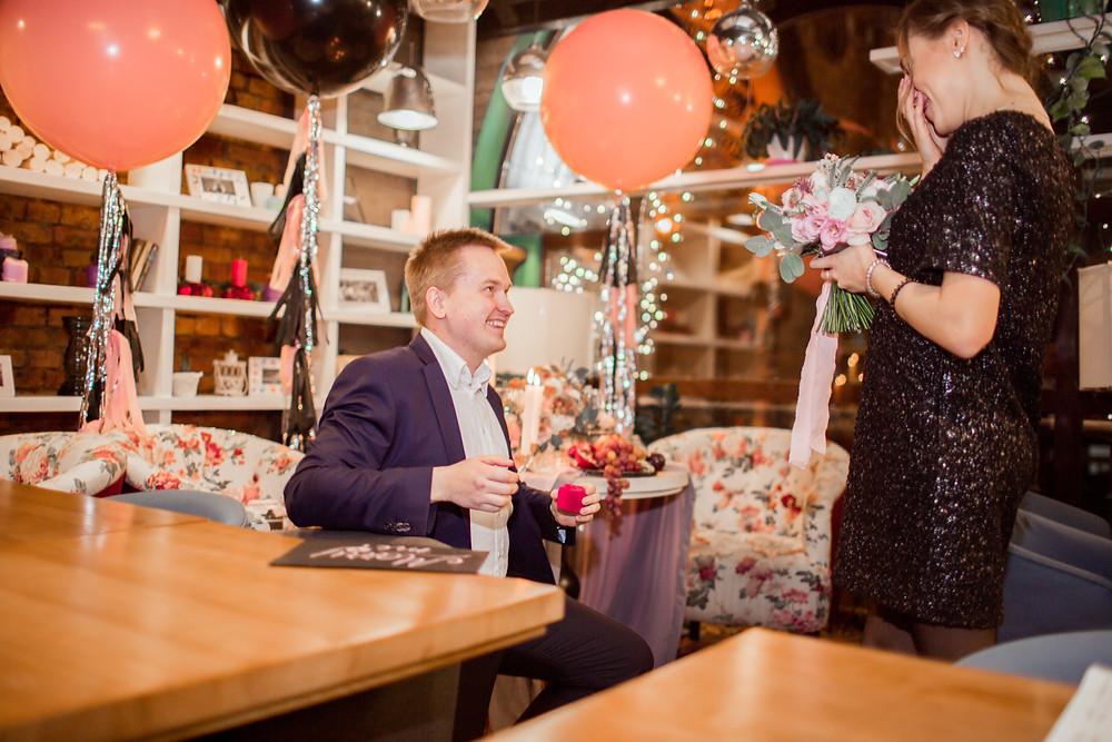 Жених на колене делает предложение невесте, протягивает обручальное кольцо
