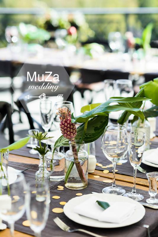 свадебная праздничная сервировка стола с использованием экзотических листьев (фикус, монстера) и маленьких ананасов, золотистое конфетти, тропическая свадьба
