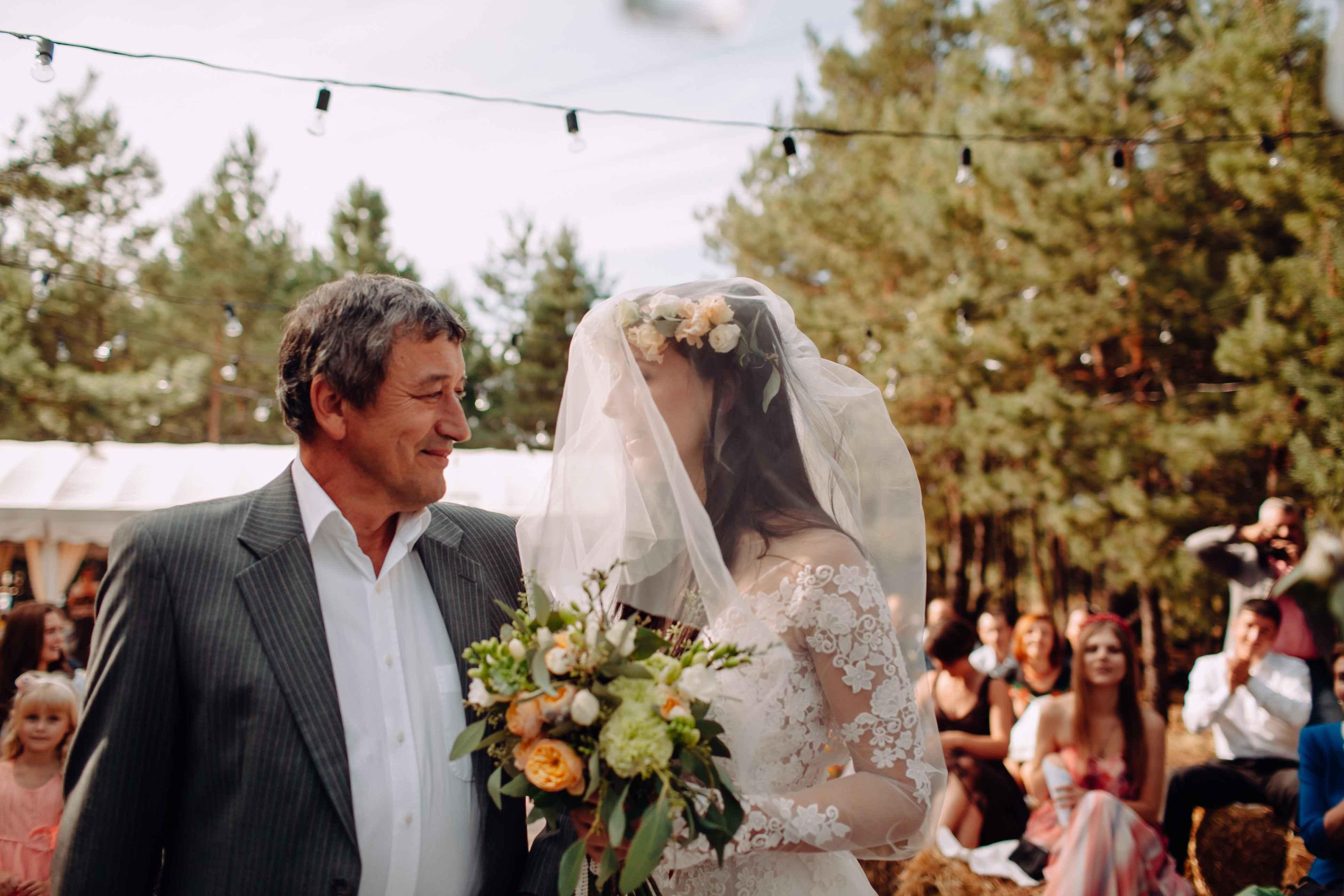 отец ведет невесту-дочь на церемонии