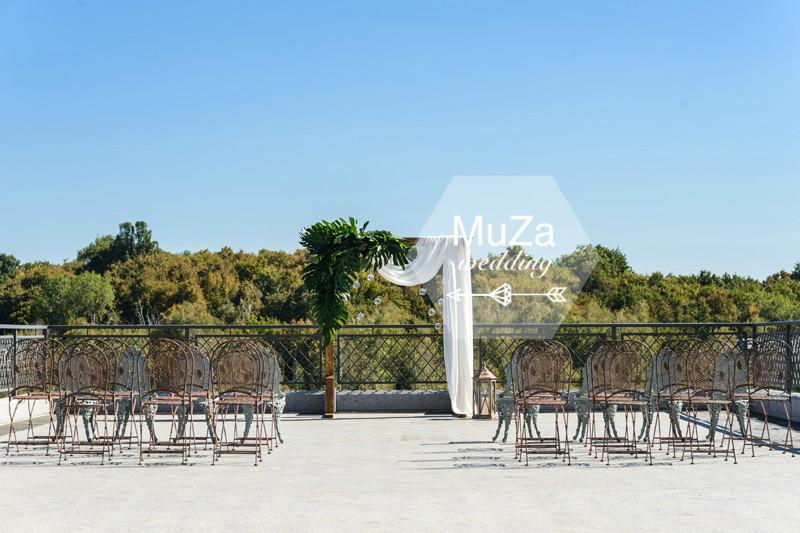 Шикарный вид, шикарная зона церемонии, легкая свадебная арка с листьями монстеры и легкой тканевой драпировкой, изящные стулья из ковки. Организация свадьбы в Киеве - свадебное агентство MuZa-wedding, тропическая свадьба