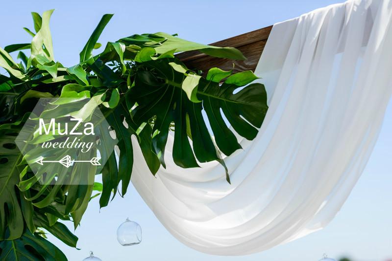 Минималистично и лаконично: свадебная арка из деревянных брусьев, нежная тканевая драпировка, листья монстеры, стеклянные шары флорариумы. Свадебный организатор - MuZa-wedding